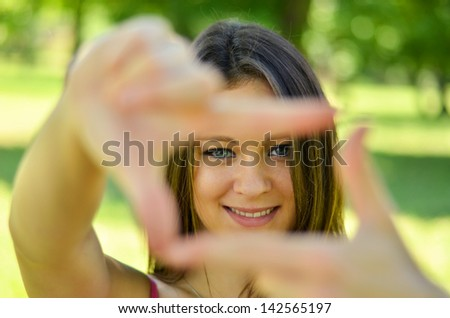 Beautiful girl making frame with hands while outdoors - stock photo