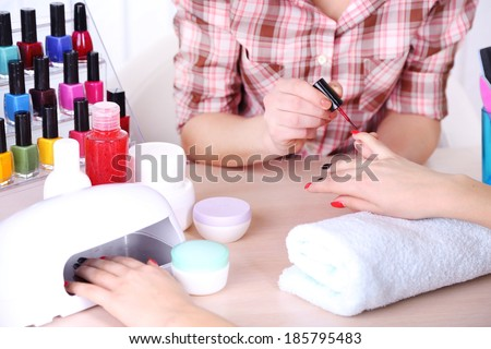 Beautiful girl manicurist doing manicure for woman in beauty salon - stock photo