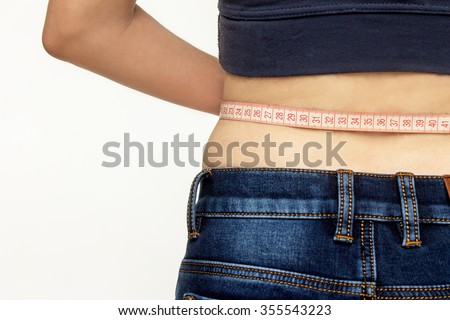 Beautiful girl measuring her waist with a measuring tape - stock photo