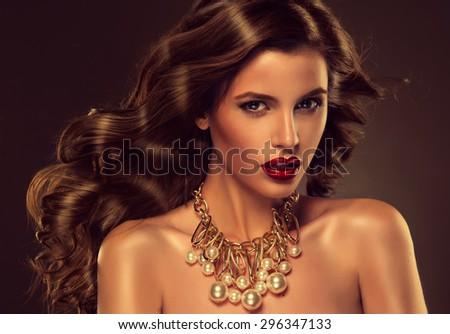 Beautiful girl model with long brown curled hair with large necklace - stock photo
