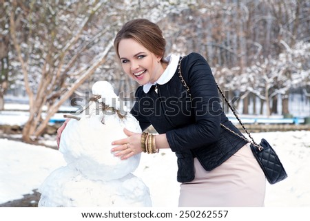 Beautiful girl near a snowman. - stock photo
