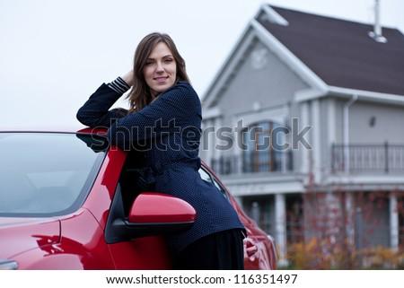 beautiful girl near the car against his house - stock photo