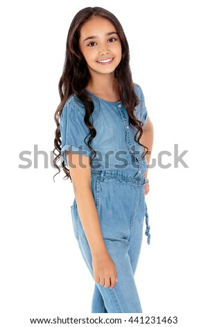Beautiful girl of school age with long dark hair,denim overalls - Isolated on white background - stock photo