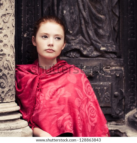 beautiful girl on a background of the old city walls - stock photo