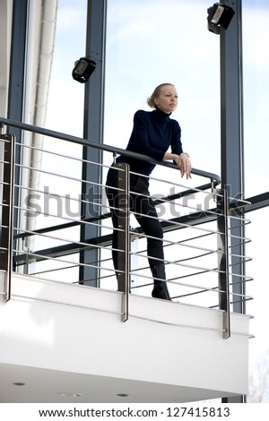 Beautiful girl on a balcony in the sky - stock photo