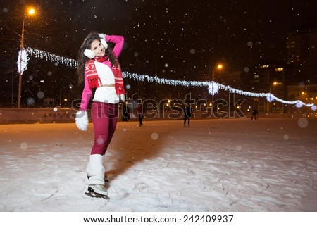 beautiful girl on a skating rink in the winter evening - stock photo