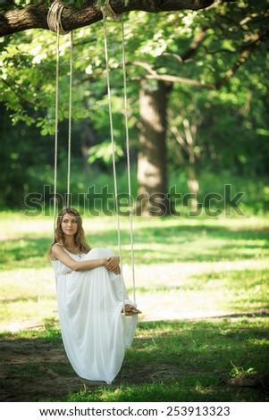 Beautiful girl on a swing - stock photo
