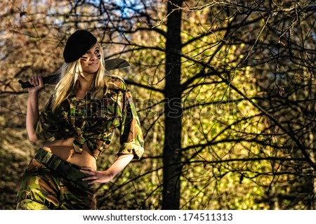Beautiful girl on camouflage outfit with machete on forest - stock photo