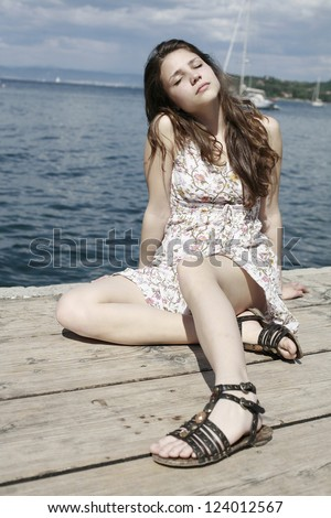 beautiful girl on sea pier, with closed eyes, looks great - stock photo