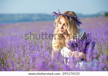 Beautiful girl on the lavender field. Beautiful blonde woman in the lavender field on sunset. - stock photo
