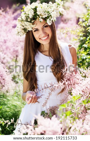 Beautiful girl on the nature in wreath of white flowers - stock photo