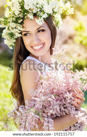 Beautiful girl on the nature in wreath of white flowers with bouquet of flowers - stock photo