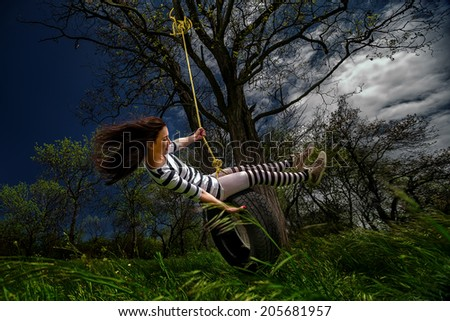 Beautiful girl on the swing in the forest  - stock photo