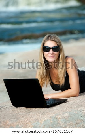 Beautiful girl outdoors with laptop lying on a rock - stock photo