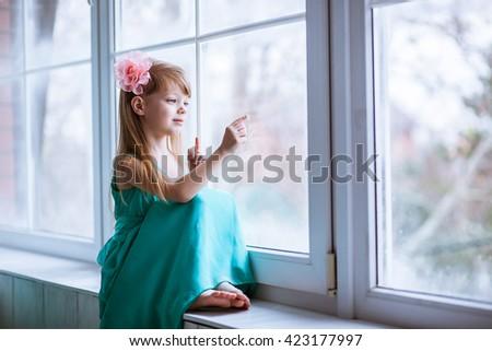 Beautiful girl paints on window glass finger - stock photo