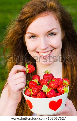 Beautiful girl pick up a strawberry from a bowl, focus on the eyes - stock photo