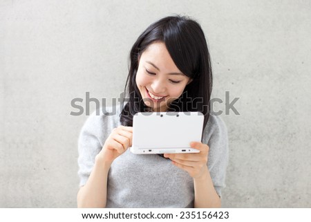 beautiful girl playing portable video game against concrete wall - stock photo