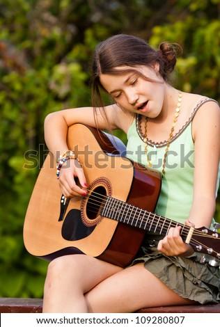 Beautiful girl playing the guitar outdoors - stock photo