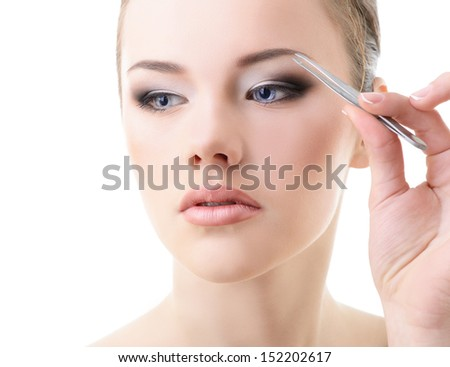 Beautiful girl plucking eyebrows with tweezers over white - stock photo