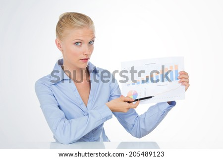 beautiful girl pointing a graphic growing on a board - stock photo