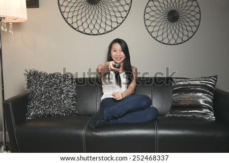 beautiful girl portrait sitting in the sofa of a living room - stock photo
