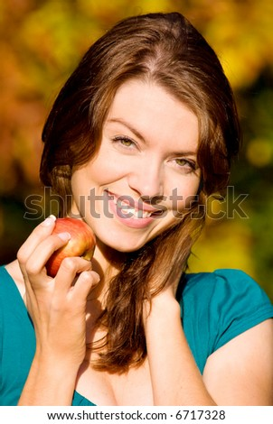 beautiful girl portrait with an apple in a park - stock photo