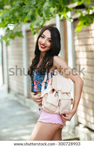 beautiful girl poses for the camera in the city on the street - stock photo