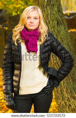 Beautiful girl poses on a park, autumn color leaves on the background, vertical format - stock photo