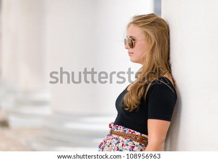 Beautiful girl posing beside the pillars of the Helsinki Cathedral - stock photo
