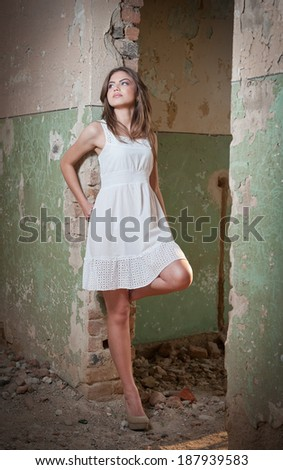 Beautiful girl posing fashion near an old wall. Pretty young woman posing laying on a wall. Very attractive blonde girl with a transparent white short dress. Romantic young woman posing - stock photo
