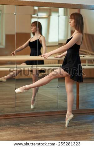 beautiful girl practicing dance holding Barre - stock photo