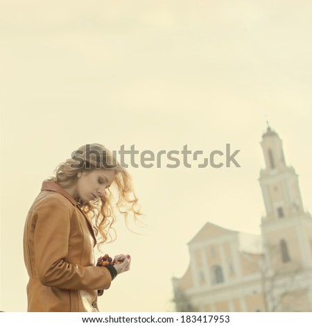 Beautiful girl praying on the background of the church - stock photo