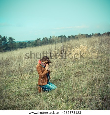 Beautiful girl praying outdoors - stock photo