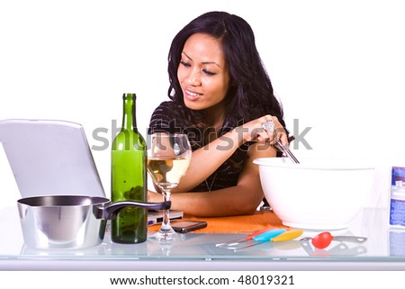 Beautiful Girl Preparing Food and Drinking Wine, Following A Recipe from the Internet - stock photo