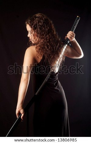 beautiful girl pulls out sword - stock photo