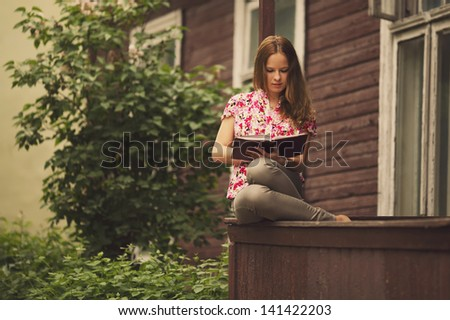 beautiful girl reading book sitting on the porch of  house - stock photo