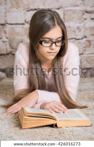 Beautiful girl reading book. Soft photo of girl with old book. education and school concept - little student girl . teen girl in glasses reading a book. reading for the summer - stock photo