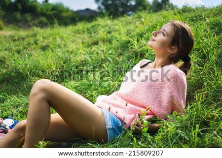 Beautiful girl relaxed in green grass, outdoor - stock photo