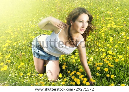 beautiful girl relaxing in the grass and flowers - stock photo