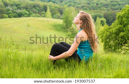 Beautiful girl relaxing on green grass. Young happy woman sitting on the hill. - stock photo