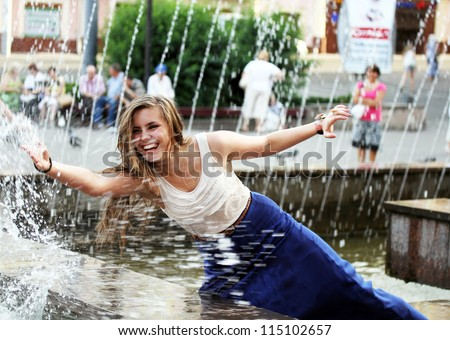 Beautiful girl relaxing with a fountain . - stock photo