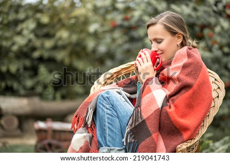 Beautiful girl resting and drinking coffee sitting in autumn garden in chair wrapped in a plaid woolen blanket. toned image - stock photo