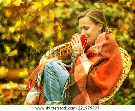 Beautiful girl resting and drinking coffee sitting in autumn garden in chair wrapped in a woolen plaid blanket. grain added - stock photo