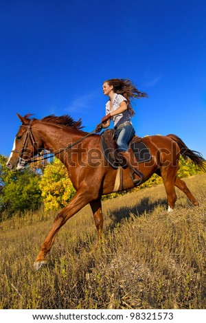 Beautiful girl riding a horse  in countryside. - stock photo