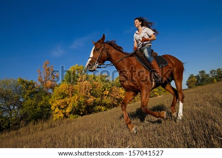 Beautiful girl  riding a horse on autumn field - stock photo