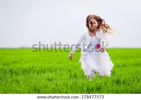 beautiful girl running in the meadow - stock photo