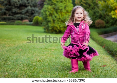 beautiful girl running on a grass in a garden - stock photo