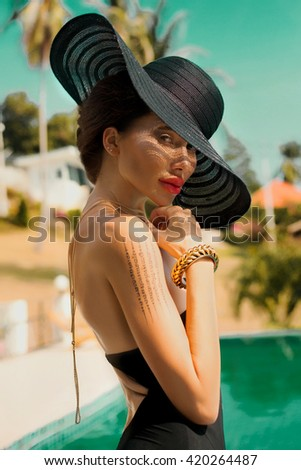 Beautiful Girl,sea style standing near pool.Travel and Vacation.Freedom Concept.Sensual brunette beautiful woman,Girl with perfect body and stylish hairstyle ,Marine style,black hat,elegant,bracelet - stock photo