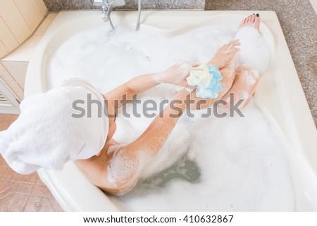 Beautiful girl showering and washing hands in bathtub. - stock photo