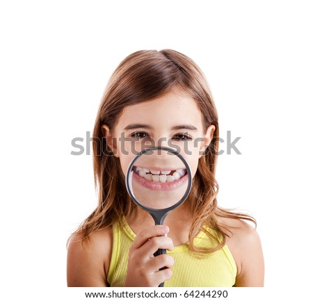 Beautiful girl showing teethes through a magnifying glass - stock photo